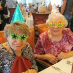 Two celebrating guests wearing their party hats, fun glasses, and big smiles.