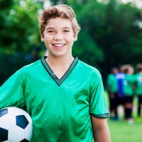 Teenage male soccer player smiles at the camera after winning the game. He is wearing a green uniform and holding a soccer ball. He has tousled brown hair. His team and coach are in a huddle in the background.