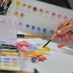 Artist's hand applying paint gouache on the drawing sheet